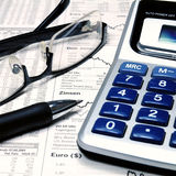 Stock Market Analysis. Calculator, glasses and a ball pen on top of a stock market report royalty free stock photography