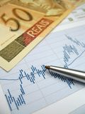 Stock market analysis. Stock market charts for investor analysis, with Brazilian Real $50 bills and pen, using selective focus on graph and pen royalty free stock image