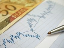 Stock market analysis. Stock market charts for investor analysis, with Brazilian Real $50 bills and pen, using selective focus on graph and pen Stock Photos