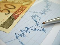 Stock market analysis. Stock market charts for investor analysis, with Brazilian Real $50 bills and pen, using selective focus on graph and pen stock photography