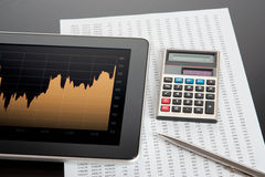 Stock Market Analyze. Modern business and stock market analyze with digital tablet, calculator, pen and printed data sheet stock image