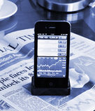 Market stock graph on Iphone 4S. Financial marketing stock graph on the Iphone 4S screen against the Financial Time newspaper in the background Royalty Free Stock Photography