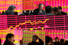 Stock market boom. Investors smiles in front of an electronic stock index board on March 2015. China's stock market is boom Stock Photos