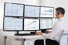 Stock Market Broker Looking At Graphs On Multiple Screens. Side view of stock market broker looking at graphs on multiple screens in office Royalty Free Stock Photos