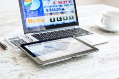 Stock market calculations and trading with a Tablet PC and Lapto. Stock market calculations with a calculator and research software on a Tablet PC with a Laptop stock photo