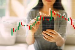 Stock market candle chart with woman using a smartphone. Stock market candle chart with woman using her smartphone in a living room royalty free stock image