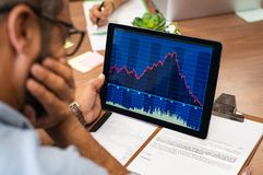 Stock market crash. Closeup of a stock market broker working with graphs on digital tablet at office. Rear view of stock agent reading bad report and graph. Back royalty free stock photo