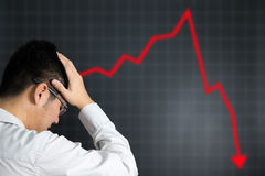 Stock market crash. Man in depression looking at stock market crashing royalty free stock photography