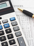 Stock market data analysis. Stock market table analysis, calculator and pen indicates research and analysis, vertical orientation, pen pointing to word 'stocks Stock Photography