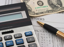 Stock market data analysis, cash. Stock market table analysis, calculator and pen indicates research and analysis, with cash, horizontal orientation, big money Royalty Free Stock Photography