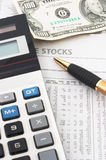 Stock market data analysis, financial. Stock market table analysis, calculator and pen indicates research and analysis, with cash, vertical orientation royalty free stock image