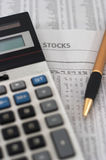 Stock market data research & analysis. Stock market table analysis, calculator and pen indicates research and analysis, vertical orientation, shallow depth of Royalty Free Stock Photo