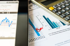 Stock market decline, analysis of the market data. A tablet pc with calculator on the table stock image