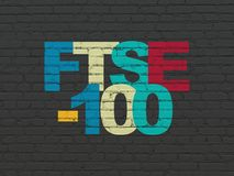 Stock market indexes concept: FTSE-100 on wall background. Stock market indexes concept: Painted multicolor text FTSE-100 on Black Brick wall background Stock Photo