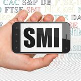 Stock market indexes concept: Hand Holding Smartphone with SMI on display. Stock market indexes concept: Hand Holding Smartphone with  black text SMI on display Stock Image
