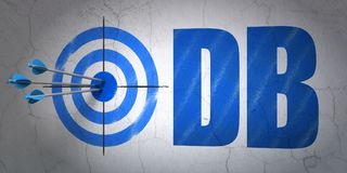 Stock market indexes concept: target and DB on wall background. Success Stock market indexes concept: arrows hitting the center of target, Blue DB on wall Royalty Free Stock Photography