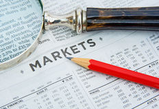 Stock market: investing. A macro  image of the financial page of a newspaper highlighting the word markets with a red pencil and magnifier Royalty Free Stock Image
