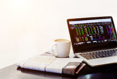 Stock market in notebook with newspaper and coffee cup Royalty Free Stock Photo
