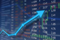 Stock market rise with blue arrow and faded candlestick charts. Winning and success emotion and happiness. Blue rising arrow stock photography
