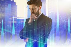 Stock market and statistics concept. Portrait of thoughtful handsome european businessman standing on abstract city background with forex chart. Stock market and stock photography