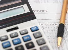 Stock market table analysis & research. Stock market table analysis, calculator and pen indicates research and analysis, horizontal orietation, shallow depth of Stock Photos