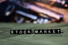 Stock market on wooden blocks. Business and finance concept. Cross processed image with bokeh background royalty free stock images