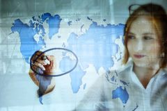 Stock market and the world map. Young business woman doing stock market analysis and marking the crisis area on the world map Stock Images