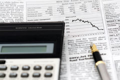 Stock markets. A calculator and a pen on top of a newspaper open at the stock market Stock Images