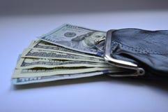 Stock mit 100 Dollarscheinen aus einer schwarzen Geldbörse heraus Stockfotos