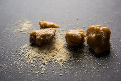 Stock Photo of Asafoetida powder / Hing or Heeng with cake and mortar Royalty Free Stock Photo