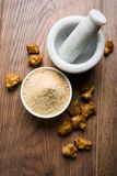 Stock Photo of Asafoetida powder / Hing or Heeng with cake and mortar Royalty Free Stock Photography