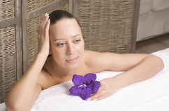 Stock photo attractive lady getting spa treatment in salon, healthcare people concept, woman with purple flower orchid Stock Photos