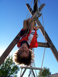 Stock Photo of Boy at Playground. First grade boy having fun at playground hanging upside down stock photography