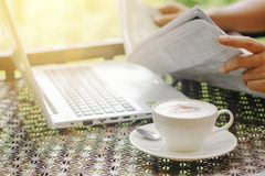 Stock photo :Cappuccino coffee cup on a vintage table with lapt Royalty Free Stock Image