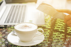Stock photo :Cappuccino coffee cup on a vintage table with lapt Royalty Free Stock Photos