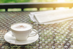 Stock photo :Cappuccino coffee with newspaper on vintage table Royalty Free Stock Photography