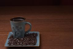 Stock photo of a cup of coffee with coffee beans. A cup of coffee sits with coffee beans Royalty Free Stock Image