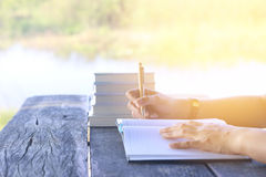 Stock Photo:female hands with pen writing on notebook on wooden Stock Images