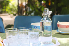 Stock Photo:Glass of water with a bottle on table Stock Photography