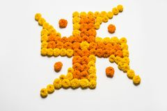 Stock photo of hindu auspicious symbol called Swastika made using marigold flower or zendu or genda phool, Flower rangoli in the s Stock Image