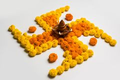 Stock photo of hindu auspicious symbol called Swastika or swastik made using marigold flower/zendu/genda phool & diwali diya / cla Stock Image