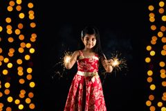 Stock photo of indian little girl holding fulzadi or sparkle or fire cracker on diwali night. Stock photo of indian little girl celebrating diwali with burning royalty free stock photography