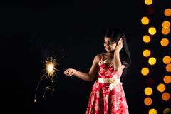 Stock photo of indian little girl holding fulzadi or sparkle or fire cracker on diwali night. Stock photo of indian little girl celebrating diwali with burning stock images