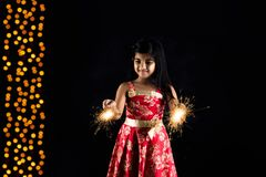 Stock photo of indian little girl holding fulzadi or sparkle or fire cracker on diwali night Stock Image