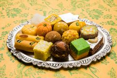 Indian sweets for diwali festival or wedding, selective focus. Stock photo of Indian sweets served in silver or wooden plate. variety of Peda, burfi, laddu in stock photos