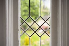 Stock Photo of a Leaded Glass Window. Photo of a leaded glass window with a garden in the background Royalty Free Stock Image