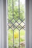 Stock Photo of a Leaded Glass Window. Photo of a leaded glass window with a garden in the background Royalty Free Stock Photos