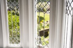 Stock Photo of a Leaded Glass Window. Photo of a leaded glass window with a garden in the background Stock Image