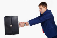 Stock-photo. man pulls portfolio. A man in a blue suit pulls portfolio Stock Image