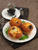 Stock-photo-muffins-with-currant. Muffins with currant and mint on white plate Royalty Free Stock Photos